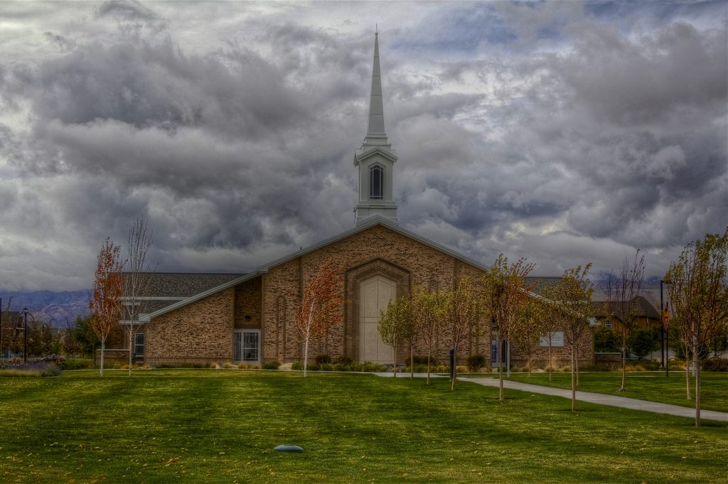 Dark clouds of trouble hanging o'er us - an LDS chapel overshadowed with foreboding clouds